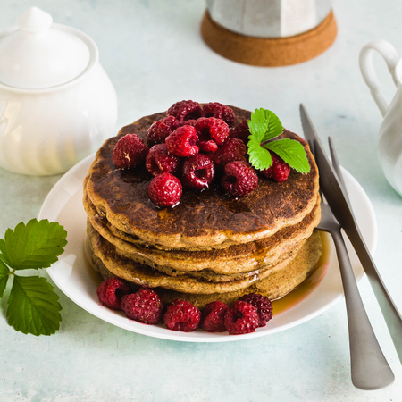 gluten-free green buckwheat pancakes with fresh berries and maple syrup. Delicious vegan breakfast without eggs, flour and refined sugar. healthy food for the whole family. Moka pot with morning coffee 스톡 콘텐츠
