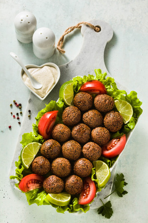 vegan falafel with cashew cheese sauce on a table with chopped tomatoes and lime slices. healthy food for the whole family or party Reklamní fotografie