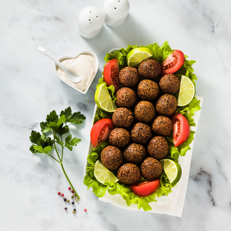 vegan falafel with cashew cheese sauce on a table with chopped tomatoes and lime slices. healthy food for the whole family or party