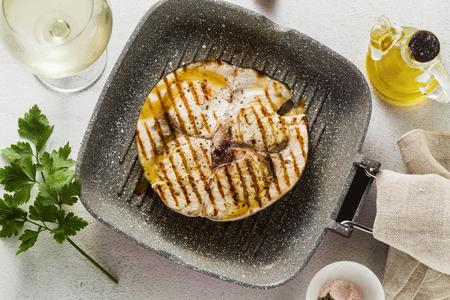 trancio di pesce spada fritto in padella con olio d'oliva e spezie. bicchiere di vino bianco