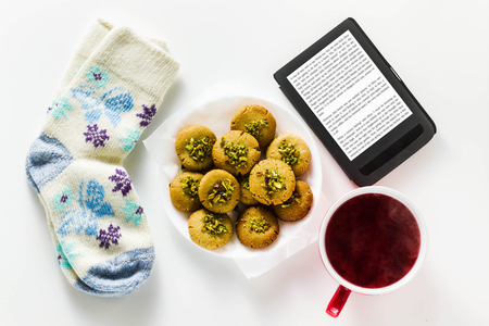 homemade cookies, almond and sesame biscuits with pistachios. healthy vegan gluten free pastries served with fresh raspberry tea. E-book and warm wool socks with a pattern. concept of winter atmospheric tea drinking with a book