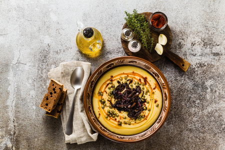 Authentic Greek Fava recipe, Middle Eastern yellow lentil soup with caramelized onions, paprika and capers. vegan healthy food in clay pots on the stone table