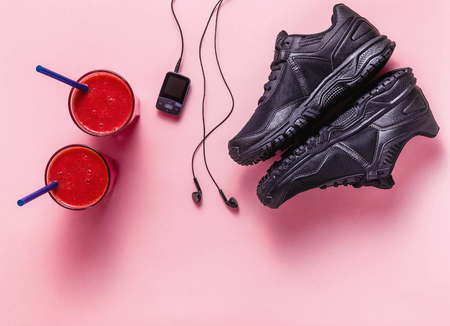 red fresh fruit smoothies, mp3 player with headphones and black sneakers on a pink background. concept of youth, music, sport and health