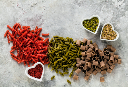 multicolor gluten-free pasta with ingredients in bowls in the form of hearts from which it is made on a stone table 免版税图像 - 113911241