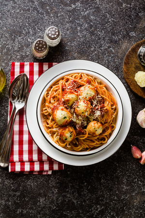 Italian pasta spaghetti with ricotta cheese balls in tomato sauce on the table with parmesan cheese. healthy traditional italian food for the whole family, party or restaurant menu Stockfoto