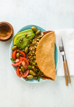 vegan breakfast of gluten-free egg-free chickpea omelet with fried mushrooms and leek. and a salad of fresh ripe tomatoes, avocados, olives and capers. healthy food for the whole family, party or restaurant menu. and a cup of italian coffee espresso