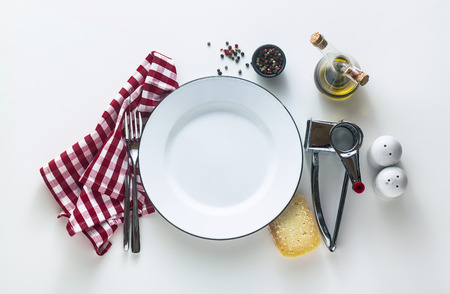 white enamelled empty plate on the table with a red checkered napkin and parmesan cheese with its grater. Typical Mediterranean style Reklamní fotografie