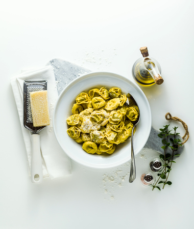 plate of italian ravioli with parmesan cheese on the plate of italian cooked ravioli tortellini with parmesan cheese on the table. healthy Mediterranean foodtable. healthy Mediterranean food