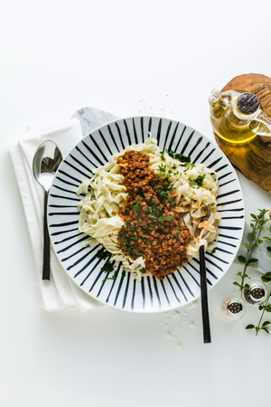 vegan pasta with lentil and tomato sauce in a plate on the table. healthy food