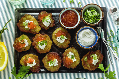 Russian traditional potato pancakes served with red caviar, green onions and sour cream on a tray with white wine and lemon