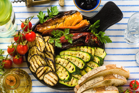 grilled vegetables on the table with white wine, fresh bread and aromatic herbs. summer menu