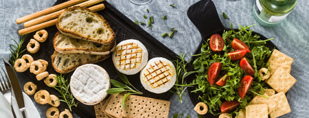 banner of grilled Italian Tomino cheese served on a table with white wine, crackers, grissini and taralli with aromatic herbs and arugula and tomato salad on a blue linen festive tablecloth. summer menu 版權商用圖片