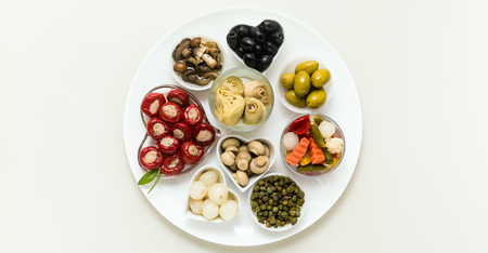 banner of Italian traditional pickles on a plate. tuna stuffed peppers, artichokes in oil, olives, mushrooms, capers. copy space. Stock Photo