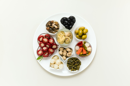 Italian traditional pickles on a plate. tuna stuffed peppers, artichokes in oil, olives, mushrooms, capers. copy space. Stock Photo