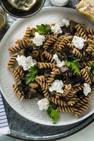 gluten-free pasta from half-wheat farro flour with portobello mushrooms and ricotta cheese on a tray on a marble table. healthy vegetarian recipes