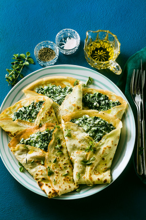 Traditional Italian pancakes crepes with spinach and ricotta on a served blue table. healthy vegetarian diet