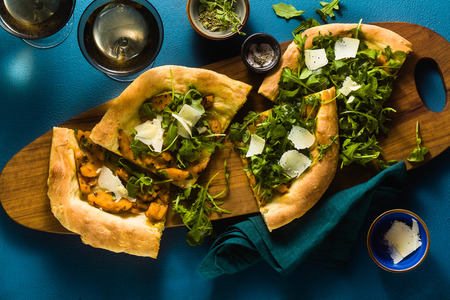 traditional Italian white pizza with taleggio and pecorino cheese, caramelized pumpkin and arugula on the blue table