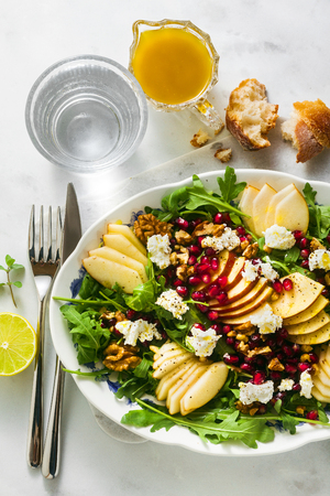 Pomegranate & Pear Green Salad with Ginger Dressing on white marble . healthy breakfast or lunch