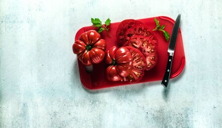 sliced Beefsteak tomato on a red cutting board and a knife. cooking healthy summer meals Stok Fotoğraf