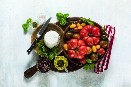 ingredients for the preparation of summer salad of colorful tomatoes, olives and ricotta. Mediterranean recipes