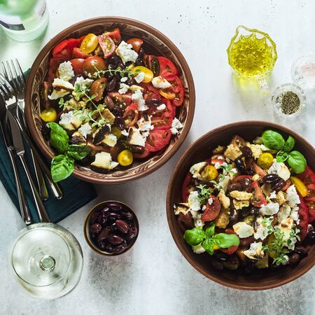Italian traditional Tuscan panzanella salad with fresh tomatoes and cheese in clay plates and white wine in a bottle and glasses . authentic Mediterranean healthy food