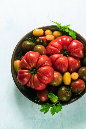 multicolored tomatoes of different colors, shapes and sizes in a clay plate on the table. Summer background