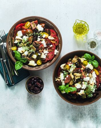 Italian traditional Tuscan panzanella salad with fresh tomatoes and cheese in clay plates. authentic Mediterranean healthy food
