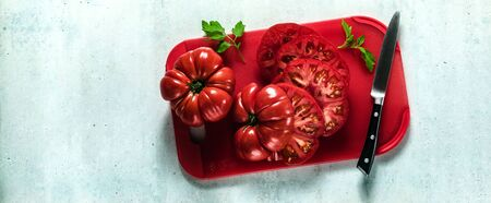 banner of sliced Beefsteak tomato on a red cutting board and a knife. cooking healthy summer meals