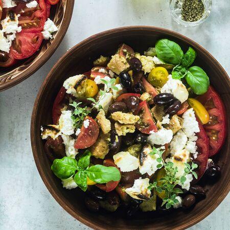Italienischer traditioneller toskanischer Panzanella-Salat mit frischen Tomaten und Käse in Tonplatten. authentisches mediterranes gesundes Essen