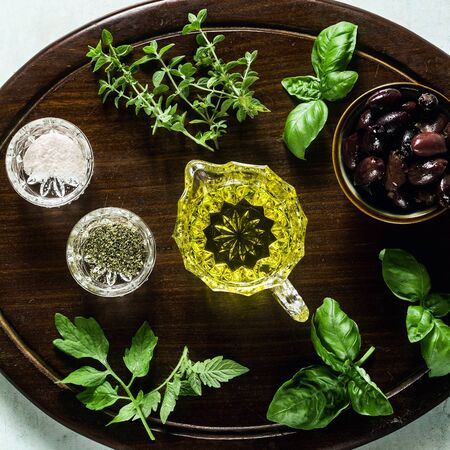 aromatic herbs for cooking and olive oil on a wooden board on the table. ingredients in the kitchen Stok Fotoğraf