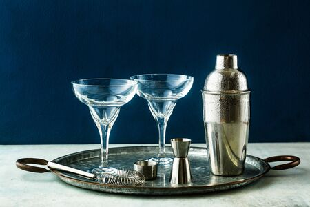 empty margarita cocktail glasses on a table with bar accessories