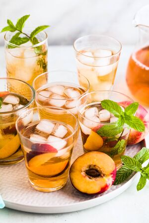 cold summer tea with peach and mint in glasses on the table