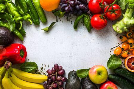 Frisches Gemüse und Obst auf einem weißen Küchentisch. Hintergrund für Supermärkte, frische Lebensmittelgeschäfte, Lieferung.
