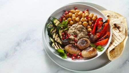 Italian Mediterranean Buddha bowl with Baba ghanoush caramelized onions, spicy chickpeas and grilled vegetables. healthy vegan food and pita bread Stock Photo