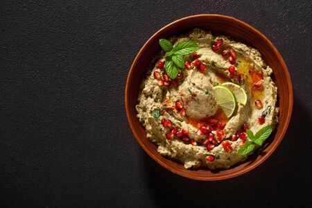 homemade spread of baked eggplant baba ganoush in a bowl with pomegranate seeds, lime, olive oil and lime slices on a black background