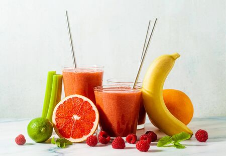 fresh smoothie juice in glasses with metal tubes on the table and ingredients. healthly food