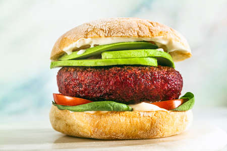 vegan burger without meat with avocado, tomatoes and spinach on the table and red wine in a glass 写真素材