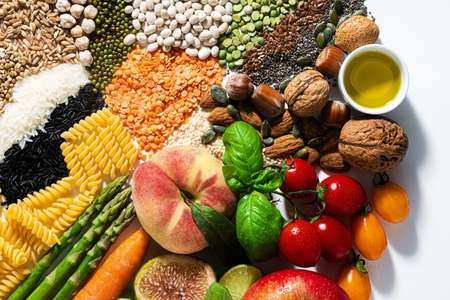 basic vegan ingredients and products. cereals, legumes, fresh vegetables and fruits, oils, seeds and nuts. balanced healthy diet isolated on white