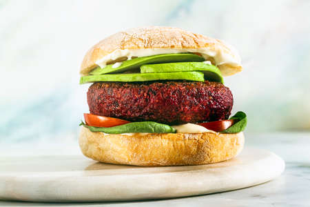 vegan burger without meat with avocado, tomatoes and spinach on the table and red wine in a glass