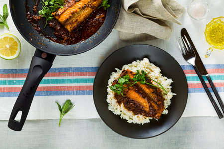 fillet of pink salmon in tomato-coconut sauce in a non-stick frying pan with parsley on a table with a linen tablecloth. healthy family food with basmati rice