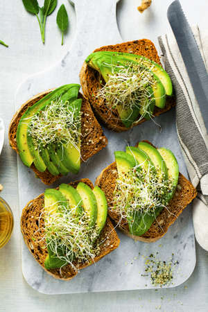 homemade tomato bread sandwiches with seeds and sun-dried tomatoes, served with avocado, sprouts and hemp seeds. a healthy morning breakfast or snack 版權商用圖片