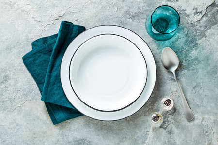 table setting with set of empty plates on stone background