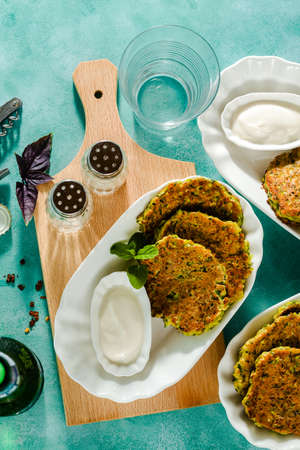 salted pancakes with zucchini and chickpea flour with spicy yoghurt sauce with beer on the table. summer vegan snack for family or lunch for friends 版權商用圖片 - 154002144