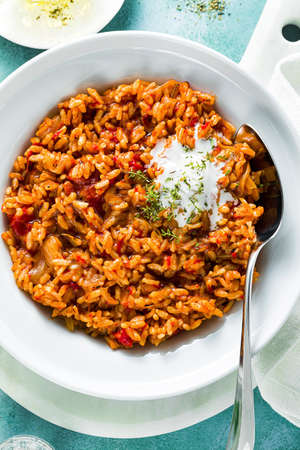 risotto with caramelized onions, tomatoes and coconut cream on a plate on the table. mix of Asian and Mediterranean cuisine