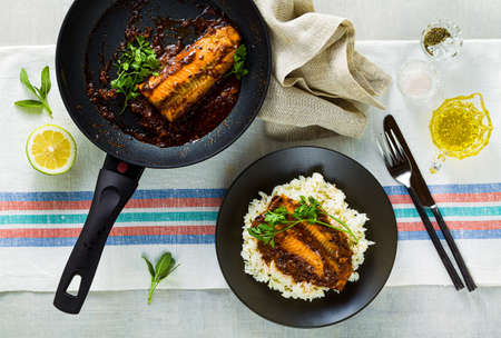 fillet of pink salmon in tomato-coconut sauce in a non-stick frying pan with parsley on a table with a linen tablecloth. healthy family food with basmati rice 版權商用圖片 - 154002153