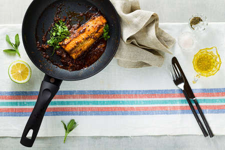 fillet of pink salmon in tomato-coconut sauce in a non-stick frying pan with parsley on a table with a linen tablecloth. healthy family food