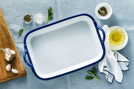 table setting with empty ceramic baking dish on a blue linen tablecloth