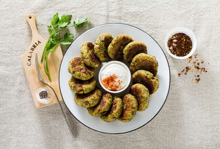 delicious vegan eggplant cutlets with yogurt and hot pepper sauce, cuisine of the Calabria region in Italy on a linen tablecloth on the table