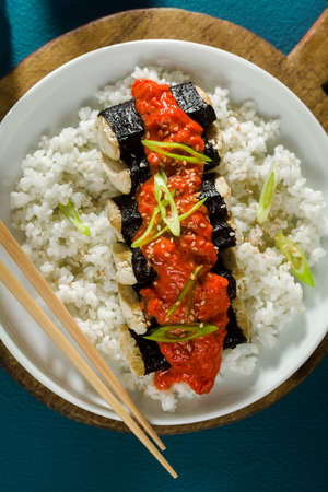 fried tofu wrapped in nori with tomato-coconut sauce and rice for sushi. vegan modern cuisine