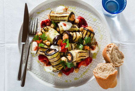 grilled eggplant wrap with red bell pepper hummus and spicy yogurt on the table. delicious vegan recipe 写真素材